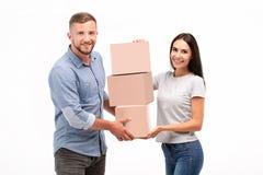 有吸引力的年轻在白色背景的夫妇运载的移动的箱子 免版税图库摄影