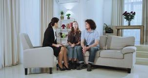有吸引力的年轻夫妇和一名美丽的不动产房地产经纪商妇女开关于大宽敞生活的一次会议在a以后 影视素材