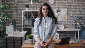 有吸引力的年轻女人身分画象在办公室单独看的照相机的 影视素材