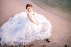 有吸引力的年轻新娘穿戴婚礼礼服和白色面纱,在海海滩单独站立 免版税库存照片