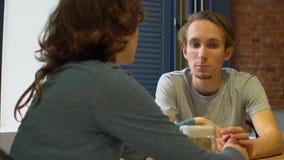 有吸引力的年轻行家夫妇谈话在与mediterrian样式的咖啡馆 股票录像
