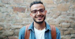 有吸引力的年轻阿拉伯微笑的看的照相机画象在砖墙附近的 影视素材