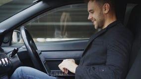 有吸引力的微笑的人键入的便携式计算机,当坐在他的汽车里面户外时 免版税库存图片
