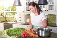 有吸引力的微笑的妇女切口菜在她晴朗的厨房里 库存图片