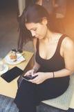 有吸引力的拉丁女性键入的正文消息,当在网络聊天由手机时 免版税图库摄影