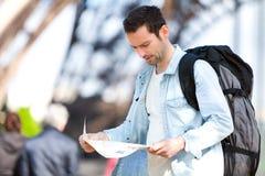 年轻有吸引力的旅游读书地图在巴黎 免版税库存照片