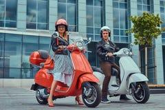 有吸引力的浪漫夫妇,一个英俊的人和性感的女性,站立与两辆减速火箭的意大利滑行车反对a 免版税库存照片