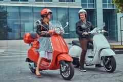 有吸引力的浪漫夫妇,一个英俊的人和性感的女性,站立与两辆减速火箭的意大利滑行车反对a 免版税库存图片