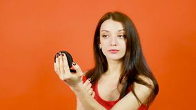 有吸引力的深色的少妇油漆她的使用红色唇膏和拿着黑镜子的嘴唇手中在明亮的桔子 影视素材