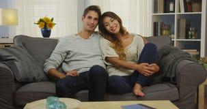 有吸引力的混合的族种夫妇坐长沙发微笑 免版税库存照片