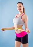 有吸引力的照相机特写镜头健身增强的微笑衡量妇女 免版税库存图片