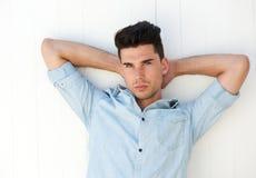 有吸引力的男性时装模特儿用在头后的手 免版税库存图片
