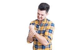 有吸引力的男性模型在痛苦中的握他的腕子 免版税库存图片