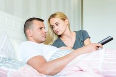 有吸引力的白种人夫妇在床上 供以人员观看的电视,爱恋看他的妇女,希望受到他的注意 免版税库存照片