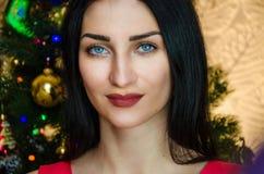 有吸引力的白种人微笑的妇女黑色头发画象在演播室射击的 有蓝眼睛的白种人女孩在圣诞节附近 库存图片