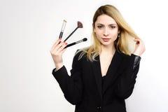 有吸引力的白肤金发的化妆师藏品刷子 免版税库存照片