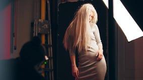 有吸引力的白肤金发的女性模型在照片演播室-摄影师工作  股票视频