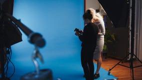 有吸引力的白肤金发的女性模型在照片演播室-摄影师工作  库存图片