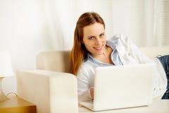 有吸引力的膝上型计算机位于的沙发妇女 免版税库存图片