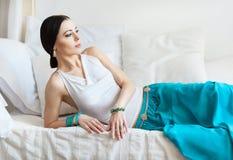 有吸引力的年轻人东方首饰的被晒黑的妇女在一张白色床上说谎 免版税库存照片