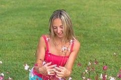 有吸引力的年轻人微笑的美丽的卷曲金发亭亭玉立的女孩塑造在摆在桃红色的T恤杉的画象看起来去镇静神色,  免版税库存照片