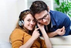 有吸引力的年轻夫妇听的音乐一起在他们的生活 库存照片