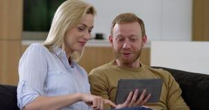 有吸引力的年轻夫妇在客厅,冲浪在微型片剂的网 股票视频