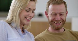 有吸引力的年轻夫妇在客厅,冲浪在片剂的网 影视素材