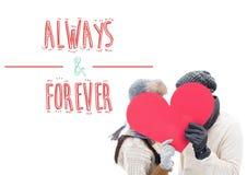 有吸引力的年轻夫妇的综合图象在拿着红色心脏的温暖的衣裳的 库存照片