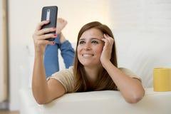 有吸引力的30岁使用在家庭沙发长沙发的妇女采取与手机的selfie画象 库存图片