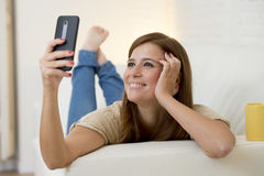 有吸引力的30岁使用在家庭沙发长沙发的妇女采取与手机的selfie画象 免版税库存图片