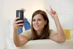 有吸引力的30岁使用在家庭沙发长沙发的妇女采取与手机的selfie画象 图库摄影