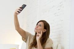 有吸引力的30岁使用在家庭沙发长沙发的妇女采取与手机的selfie画象 库存照片