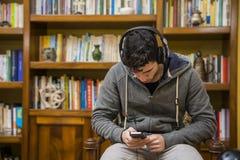 有吸引力年轻人坐的听到在一套的音乐立体声耳机 免版税库存照片