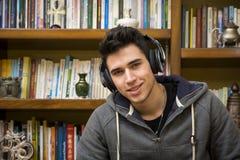 有吸引力年轻人坐的听到音乐 免版税库存照片