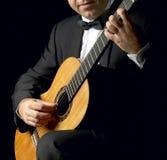 有吸烟服的古典吉他弹奏者 免版税图库摄影