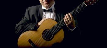 有吸烟服的古典吉他弹奏者 免版税库存图片