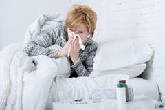 有吹在遭受冷的流感病毒症状的床上的组织的打喷嚏的鼻子的妇女有医学压片药片 免版税库存图片