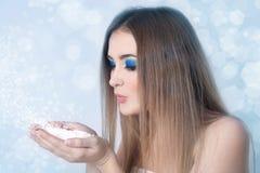 有吹在雪的明亮的蓝色构成的女孩 免版税库存照片