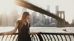 有吹在风的头发的美丽的白种人少妇摆在为在惊人的日落河码头纽约4K的照相机 影视素材
