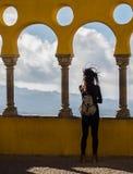 有吹由风的头发的妇女站立在阳台 库存图片
