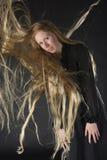 有吹通过长的头发的风的白肤金发的妇女 免版税图库摄影