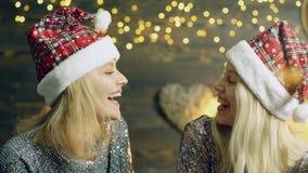 有吹雪的冬季衣服的愉快的年轻女人以光为背景 新年的帽子的女孩 股票录像