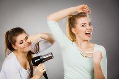 有吹风器的妇女干燥朋友腋窝 免版税库存图片