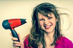 有吹风机的时尚女孩烘干她的头发-减速火箭的样式 免版税库存图片