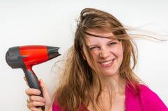 有吹风机的时尚女孩烘干她的头发 免版税图库摄影