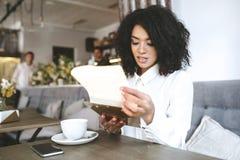 有周道地看在菜单的黑暗的卷发的小姐非裔美国人的女孩咖啡馆画象有杯子的在桌上 免版税库存照片