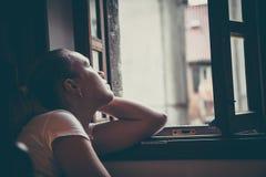 有周道的表示的孤独的沉思妇女在想法丢失了认为和看在葡萄酒样式的被打开的窗口的与微量 库存图片