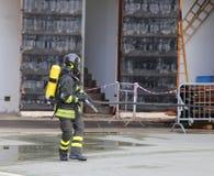 有呼吸器官和氧气瓶奔跑的消防队员 免版税图库摄影