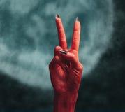 有和平手标志的恶魔手 图库摄影